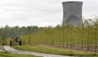 """FILE - In this May 18, 2011, file photo, a worker is seen in the area surrounding a tree farm in North Perry, Ohio, near the two cooling towers of the Perry Nuclear Power Plant looming in the background. Amid intense scrutiny of the roles company officials played in an alleged $60 million bribery scheme to obtain a $1 billion bailout for two aging nuclear power plants, Ohio's largest electric utility has announced a goal to become """"carbon neutral"""" by 2050 while reducing greenhouse gas emissions 30% by 2030. (AP Photo/Amy Sancetta, File)"""
