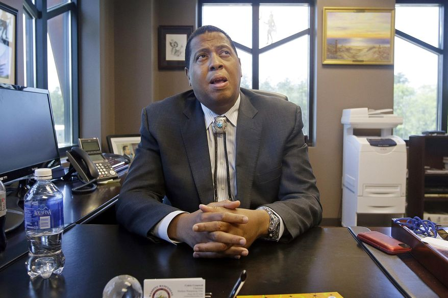 FILE - In this May 29, 2014 photo, Mashpee Wampanoag Tribe Chairman Cedric Cromwell sits behind his desk at the government center in Mashpee, Mass. Cromwell and the owner of a Rhode Island architecture firm were arrested Friday, Nov. 13, 2020, and charged in a bribery scheme involving the tribe's plans to build a resort casino in Taunton, Mass. (AP Photo/Stephan Savoia, File)