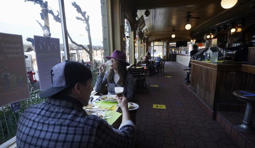 Mitchell Bryant, left, and Darla Scott eat inside at the Buena Vista Cafe during the coronavirus outbreak in San Francisco, Thursday, Nov. 12, 2020. California on Thursday became the second state — behind Texas — to eclipse a million known cases, while the U.S. has surpassed 10 million infections, according to data compiled by Johns Hopkins University.(AP Photo/Jeff Chiu)