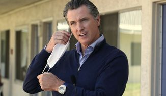 FILE - In this June 30, 2020, file photo, Gov. Gavin Newsom removes his face mask before giving an update during a visit to Pittsburg, Calif. Newsom said in a statement Friday, Nov. 13, that he should not have attended a birthday dinner with a dozen people at the posh French Laundry restaurant last week, saying that he should have set a better example for a virus-fatigued state that is seeing steep increases in coronavirus cases. Newsom's decision to attend was made as he's been telling others to not mingle with others outside their households. (AP Photo/Rich Pedroncelli, Pool, File)