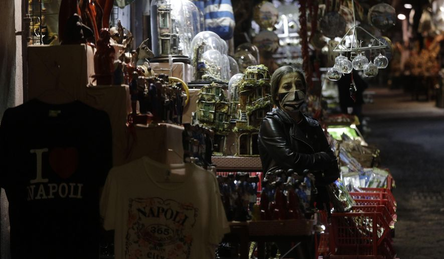 A woman stands outside her nativity scenes shop along San Gregorio Armeno street in Naples, in the Campania region, Italy, Friday, Nov. 13, 2020. The regions of Campania and Tuscany were designated red zone on Friday, signaling the dire condition of a hospitals struggling with a surge of new admissions. (AP Photo/Gregorio Borgia)