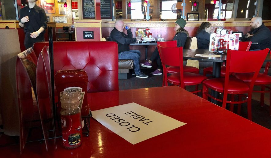 In this March 15, 2020, file photo, a Red Robin restaurant in Tigard, Ore., has closed some tables in order to maintain social distancing between diners per CDC guidelines. On Nov. 25, Oregon Gov. Kate Brown announced bars and restaurants can reopen for limited outdoor service next week but many restrictions will remain in place until a vaccine against the coronavirus is widely available. (AP Photo/Gillian Flaccus, File)  **FILE**