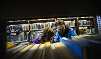 Beatrix Robb, 13, of Brattleboro, Vt., and her mother, Jen, look for a book at the Brooks Memorial Library, in Brattleboro, Vt., Friday, Nov. 13, 2020. The library plans to close its doors on Thanksgiving and reopen on Dec. 14, 2020, as the number of COVID-19 cases are on the rise in the area. (Kristopher Radder/The Brattleboro Reformer via AP)