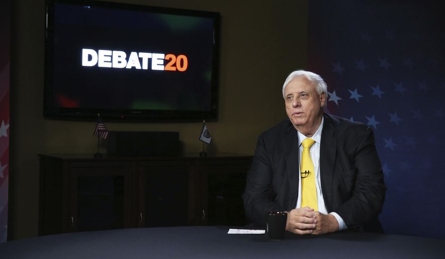 FILE - West Virginia Gov. Jim Justice prepares for a debate with Democratic challenger, Kanawha County Commissioner Ben Salango, Tuesday Oct. 13. 2020, in Morgantown, W.Va.  Justice announced on Friday, Nov. 13,  a mandatory face covering requirement indoors at businesses and all other spaces will take effect at midnight. Justice said businesses will need to post mask requirements at establishments under the rules of his executive order.(AP Photo/Kathy Batten, File)
