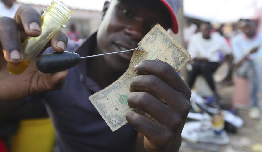 A currency trader mends an old and worn 2 dollar bill at a busy market in Harare, in this Monday, Oct, 26, 2020 photo. Worn out or shredded by rats, one dollar notes are king in Zimbabwe, beset by a continuing economic crisis.  Crisp new notes are not coming into Zimbabwe, so enterprising traders are repairing old ones for desperate customers.( AP Photo/Tsvangirayi Mukwazhi)