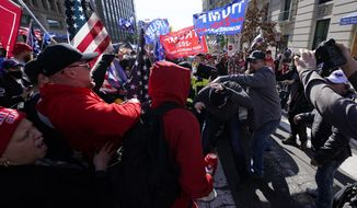 A fight breaks out as supporters of President Donald Trump and counter-protesters rally on Saturday, Nov. 14, 2020, in Washington. (AP Photo/Julio Cortez)