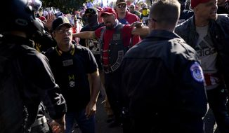 Supporters of President Donald Trump, right, clash with a counter-protester, at left in motorcycle helmet, during a rally Saturday, Nov. 14, 2020, in Washington. (AP Photo/Julio Cortez)