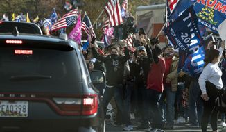 President Donald Trump drives by a group of supporters participating in a rally near the White House, Saturday, Nov. 14, 2020, in Washington. (AP Photo/Evan Vucci)