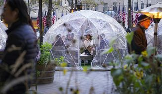 Diners sit inside a transparent dome at a restaurant while observing social distancing protocols to combat the spread of COVID-19, Saturday, Nov. 14, 2020, in New York. (AP Photo/John Minchillo)