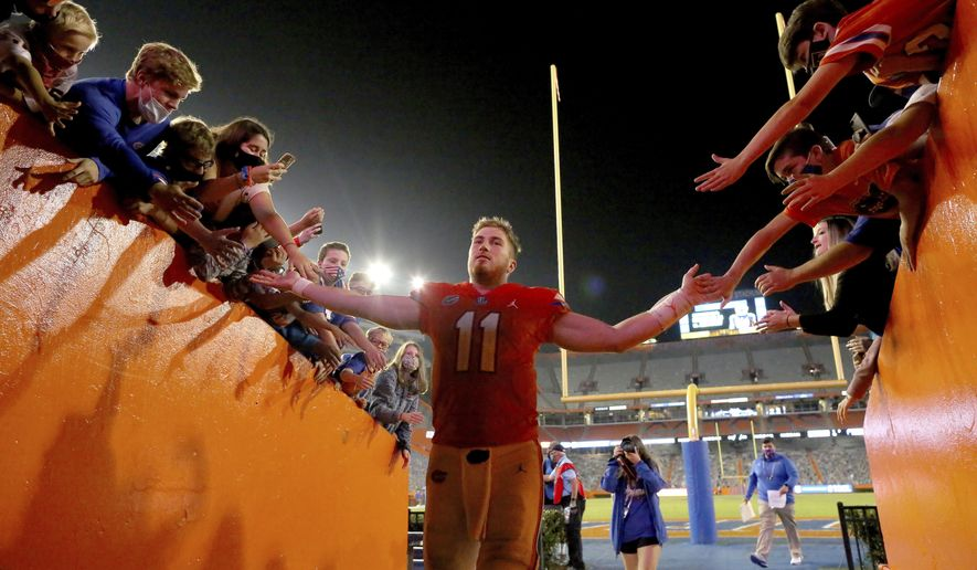 Florida quarterback Kyle Trask (11) is congratulated by fans as he leaves the field after the team's win over Arkansas in an NCAA college football game in Gainesville, Fla., Saturday, Nov. 14, 2020. (Brad McClenny/The Gainesville Sun via AP)