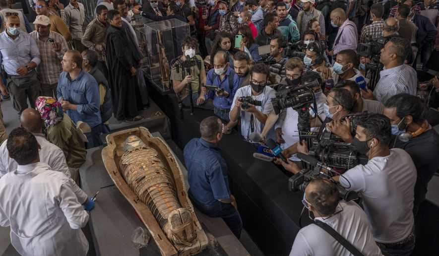 Journalists gather around an ancient sarcophagus more than 2500 years old, discovered in a vast necropolis and Mostafa Waziri, the secretary-general of the Supreme Council of Antiquities, center, in Saqqara, Giza, Egypt, Saturday, Nov. 14, 2020. Egyptian antiquities officials on Saturday announced the discovery of at least 100 ancient coffins, some with mummies inside, and around 40 gilded statues south of Cairo. (AP Photo/Nariman El-Mofty)