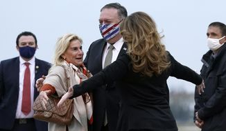 U.S. Secretary of State Mike Pompeo, center, and his wife Susan, right, embrace U.S. Ambassador to France Jamie McCourt, left, after stepping off a plane at Paris Le Bourget Airport, Saturday, Nov. 14, 2020, in Le Bourget, France. Pompeo is beginning a 10-day trip to Europe and the Middle East. (AP Photo/Patrick Semansky, Pool)