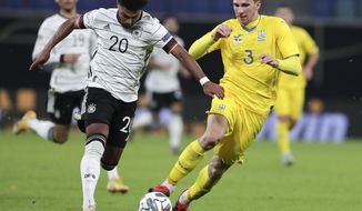 Germany's Serge Gnabry, left, and Ukraine's Ilya Zabarnyi battle for the ball during the UEFA Nations League soccer match between Germany and the Ukraine at the Red Bull Arena in Leipzig, Germany, Saturday, Nov. 14, 2020. (AP Photo/Michael Sohn)