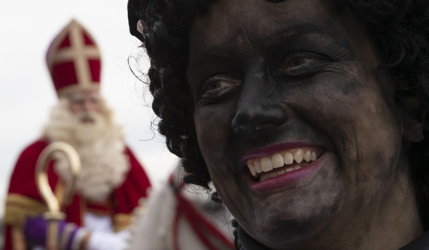 -FILE- In this Saturday Nov. 16, 2019, file image, Zwarte Piet, or Black Pete, right, the controversial blackfaced sidekick of Saint Nicholas, rear left, walks in a parade in Scheveningen harbor, near The Hague, Netherlands. Saint Nicholas, the gift-bearing patron saint of children, was arriving in the Netherlands on Saturday amid a partial coronavirus lockdown that forced the cancelation of celebrations in many towns and cities. (AP Photo/Peter Dejong, File)