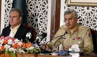 Pakistan's military spokesman Maj. Gen. Babar Iftikhar, right, briefs to media while Foreign Minister Shah Mahmood Qureshi listens during a joint press conference regarding on going tension between Pakistan and India, in Islamabad, Pakistan, Saturday, Nov. 14, 2020. Pakistani and Indian troops clashed in disputed Kashmir, causing casualties and wounding more than 30 others on both sides, officials said. The fighting came amid increasing tension between the South Asian neighbors. (AP Photo/Anjum Naveed)