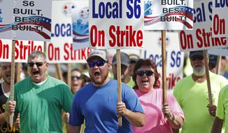 FILE - In this Saturday, July 25, 2020, file photo striking Bath Iron Works shipbuilders march in solidarity, in Bath, Maine. After a bitter two-month strike during a pandemic, BIW and its production workers are catching up on the production schedule. Machinists Union Local S6 and shipyard managers have been meeting with help from a federal mediator since the strike ended in August. (AP Photo/Robert F. Bukaty, File)