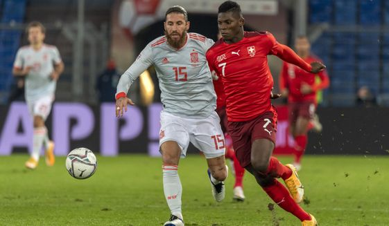 Spain's Sergio Ramos, left, fights for the ball against Switzerland's Breel Embolo during the UEFA Nations League soccer match between Switzerland and Spain at the St. Jakob-Park stadium in Basel, Switzerland, Saturday Nov. 14, 2020. (Georgios Kefalas/Keystone via AP)