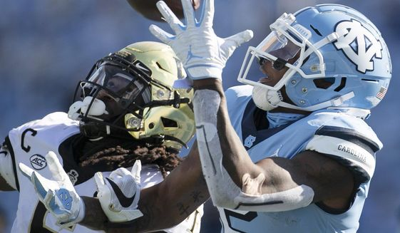 Wake Forest defense back Ja'Sir Taylor (6) defends North Carolina's Dyami Brown (2) in the first half of an NCAA college football game Saturday, Nov. 14, 2020, in Chapel Hill, N.C. Taylor intercepted the pass. (Robert Willett/The News & Observer via AP)