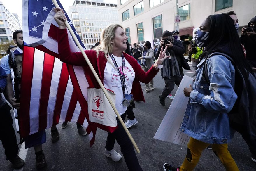 A woman gestures as she argues with a counter-protester after supporters of President Donald Trump held marches Saturday, Nov. 14, 2020, in Washington. (AP Photo/Julio Cortez)