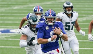 New York Giants' Daniel Jones (8) runs away from Philadelphia Eagles' Alex Singleton for a touchdown during the first half of an NFL football game Sunday, Nov. 15, 2020, in East Rutherford, N.J. (AP Photo/Seth Wenig)