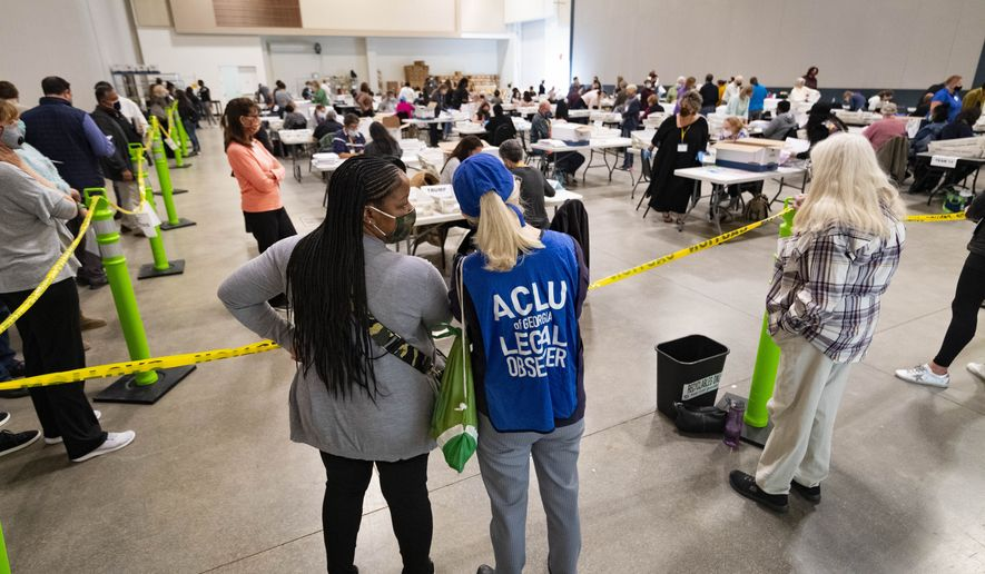 Democrat observers confer as they look on during a Cobb County hand recount of Presidential votes on Sunday, Nov. 15, 2020, in Marietta, Ga. (John Amis/Atlanta Journal & Constitution via AP)