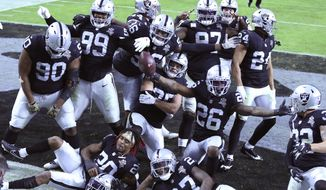 Las Vegas Raiders players celebrate a fumble recovery by Las Vegas Raiders cornerback Nevin Lawson (26) against the Denver Broncos during the second half of an NFL football game, Sunday, Nov. 15, 2020, in Las Vegas. (AP Photo/Isaac Brekken)