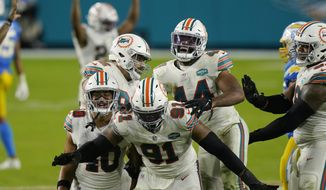 Miami Dolphins defensive end Emmanuel Ogbah (91) and his teammates celebrate after a play during the second half of an NFL football game against the Los Angeles Chargers, Sunday, Nov. 15, 2020, in Miami Gardens, Fla. (AP Photo/Lynne Sladky)