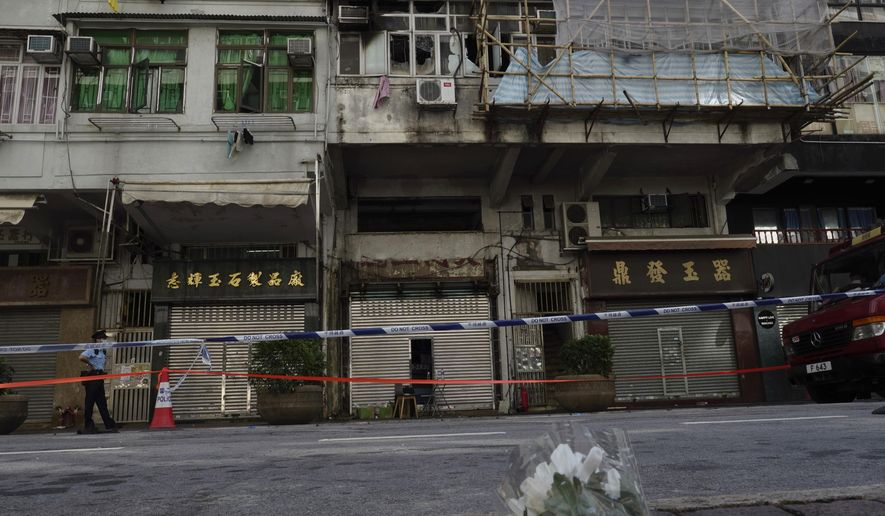 """Flowers are placed at a fire site, top center with broken windows, in Hong Kong Monday, Nov. 16, 2020. City authorities said a fire in a crowded residential district in Hong Kong has """"caused a number of deaths and injuries"""". (AP Photo/Vincent Yu)"""