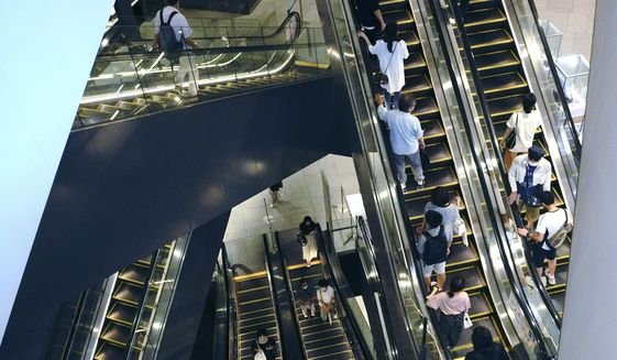 People take elevators at a shopping building in Tokyo Monday, Aug. 24, 2020. Japan's economy grew at an annual rate of 21.4% in the last quarter in a recovery from the shocks of the pandemic driven by both private spending and exports. (AP Photo/Eugene Hoshiko)