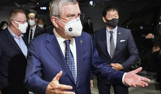 International Olympic Committee President Thomas Bach gestures on his arrival at a hotel in Tokyo Sunday, Nov. 15, 2020. IOC President Bach is beginning a visit to Tokyo to convince politicians and the Japanese public that the postponed Olympics will open in just over eight months.(Kyodo News via AP)