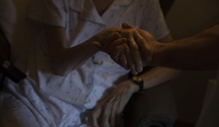 A health care worker holds the hand of a resident at the CHC nursing home in Landenne, Belgium, Wednesday, Nov. 4, 2020. (AP Photo/Virginia Mayo)