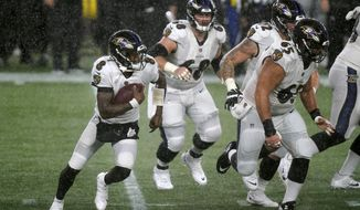 Baltimore Ravens quarterback Lamar Jackson, left, runs behind blocking by the Ravens offensive linemen in the second half of an NFL football game against the New England Patriots, Sunday, Nov. 15, 2020, in Foxborough, Mass. (AP Photo/Elise Amendola)