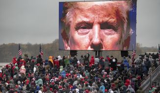 FILE - In this Oct. 27, 2020, file photo, supporters of President Donald Trump watch a video during a campaign event in Lansing, Mich. (Nicole Hester/Mlive.com/Ann Arbor News via AP, File)