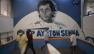 Residents enter a school where a mural of Brazil's late Formula One driver Ayrton Senna covers the wall during municipal elections, at a polling station in the Rocinha slum of Rio de Janeiro, Brazil, Sunday, Nov.15, 2020. Voters across Latin America's biggest country are electing mayors and municipal council members. (AP Photo/Silvia Izquierdo)