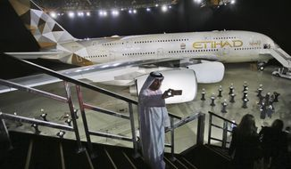 FILE- In this Dec. 18, 2014, file photo, an Emirati man takes a selfie in front of a new Etihad Airways A380 in Abu Dhabi, United Arab Emirates. Etihad Airways, the national airline of the United Arab Emirates, announced Monday, Nov. 16, 2020 it would start operating daily nonstop flights to Tel Aviv next spring, a move that deepens ties between the UAE and Israel after the two countries agreed to normalize relations. (AP Photo/Kamran Jebreili, File)