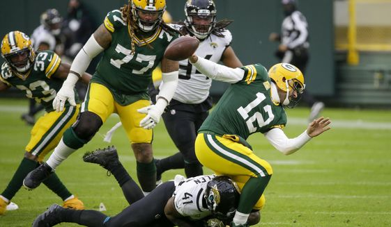 Jacksonville Jaguars' Josh Allen takes down Green Bay Packers' Aaron Rodgers during the second half of an NFL football game Sunday, Nov. 15, 2020, in Green Bay, Wis. Roughing the passer was called on the play. (AP Photo/Mike Roemer)