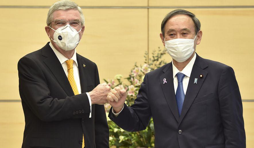 Japan's Prime Minister Yoshihide Suga, right, greets International Olympic Committee (IOC) President Thomas Bach during their meeting in Tokyo Monday, Nov. 16, 2020. (Kazuhiro Nogi/Pool Photo via AP)