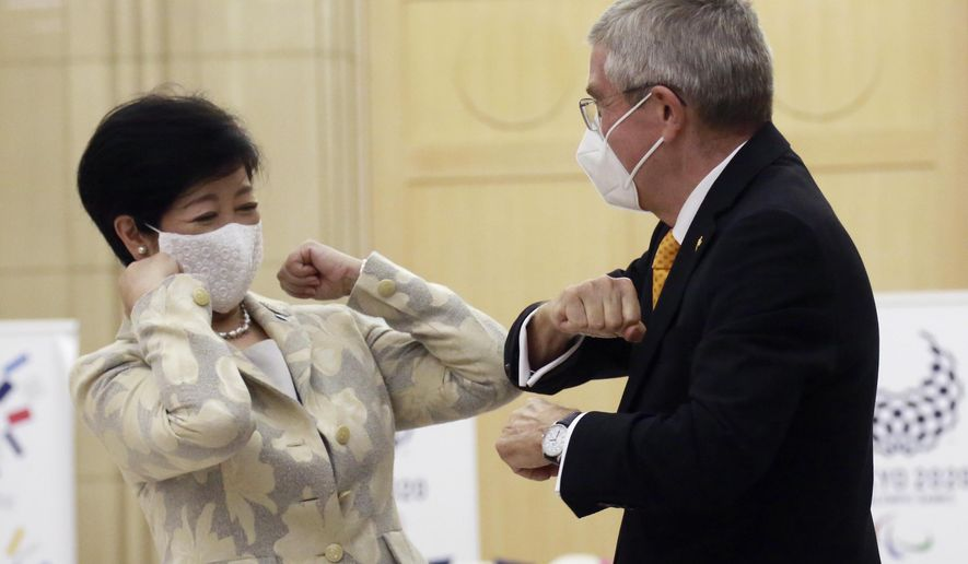 Tokyo Governor Yuriko Koike, left, greets International Olympic Committee President Thomas Bach before their meeting in Tokyo, Monday, Nov. 16, 2020. IOC President Bach is beginning a visit to Tokyo to convince politicians and the Japanese public that the postponed Olympics will open in just over eight months.(AP Photo/Koji Sasahara)
