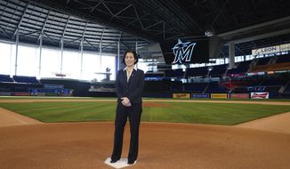 In this photo provided by the Miami Marlins, new Miami Marlins general manager Kim Ng poses for a photo at Marlins Park stadium before being introduced during a virtual news conference, Monday, Nov. 16, 2020, in Miami. Ng discussed her climb to become the first female GM in the four major North American professional sports leagues. (Joseph Guzy/Miami Marlins via AP)