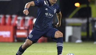 FILE - In this July 12, 2020, file photo, Sporting Kansas City midfielder Roger Espinoza pushes the ball on the pitch during the second half of an MLS soccer match against Minnesota United in Kissimmee, Fla. Espinoza understands that the United States has been consumed by the presidential election but he's disheartened by the lack of response stateside to the Hurricanes ravaging his homeland in Honduras. (AP Photo/Phelan M. Ebenhack, File)