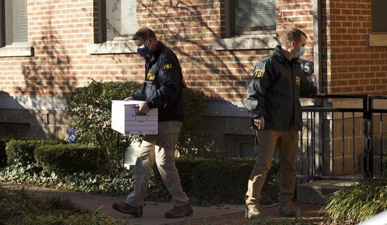 FBI agents remove items from the German Village home of Public Utilities Commission of Ohio Chairman Sam Randazzo in Columbus, Ohio on Monday, Nov. 16, 2020. (Adam Cairns/The Columbus Dispatch via AP)