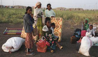 Ethiopian refugees gather n Qadarif region, easter Sudan, Sunday, Nov. 15, 2020. Thousands of Ethiopians fled the war in Tigray region into Sudan. (AP Photo/Marwan Ali)