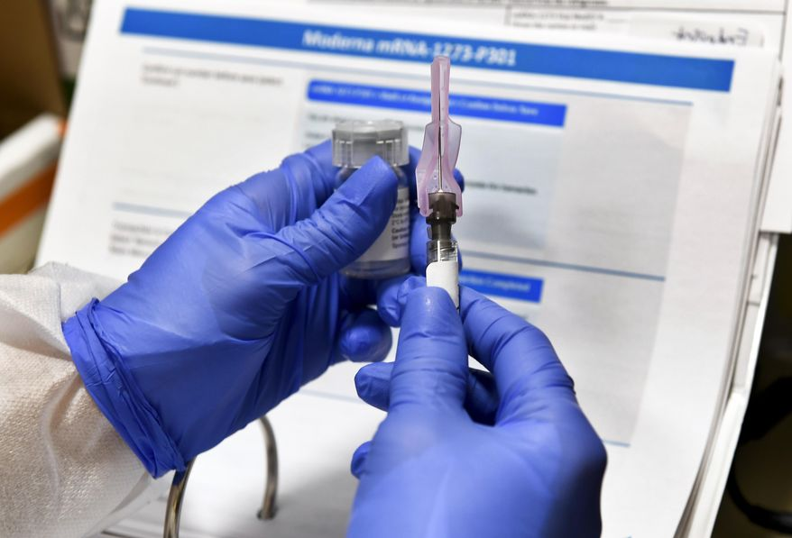 In this July 27, 2020, file photo, nurse Kathe Olmstead prepares a shot that is part of a possible COVID-19 vaccine, developed by the National Institutes of Health and Moderna Inc., in Binghamton, N.Y. Moderna said Monday, Nov. 16, 2020, its COVID-19 shot provides strong protection against the coronavirus that's surging in the U.S. and around the world. (AP Photo/Hans Pennink, File)