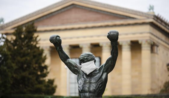FILE - In this April 14, 2020, file photo the Rocky statue is outfitted with a mock surgical face mask at the Philadelphia Art Museum in Philadelphia. Philadelphia is banning indoor dining at restaurants and plans to shutter gyms, museums and libraries as the city battles a resurgence of the coronavirus, officials announced Monday, Nov. 16. (AP Photo/Matt Rourke, File)