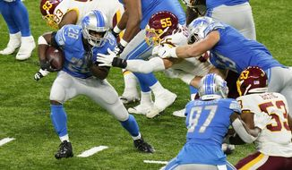 Detroit Lions running back Adrian Peterson (28) avoids Washington Football Team linebacker Cole Holcomb (55) during the second half of an NFL football game, Sunday, Nov. 15, 2020, in Detroit. (AP Photo/Carlos Osorio)