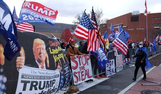 Approximately 100 Trump supporters some with flags and signs stood across West Third Street from the Federal Building in Williamsport, Pa., for hours Tuesday, Nov. 17, 2020, chanting such things as Four More Years, Black Lives Matter, We Want Trump and Dead People Cant Vote. Attorneys for the Trump campaign organization inside the Federal Building were arguing why the state and seven county election boards were arguing should not certify the results of the general election because voters across the state were not treated the same. (John Beauge/The Patriot-News via AP)