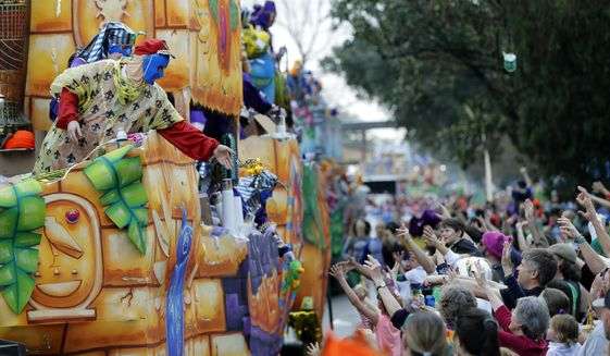 Float riders toss beads and trinkets during the Krewe of Thoth Mardi Gras parade in New Orleans.  (AP Photo/Gerald Herbert, File)