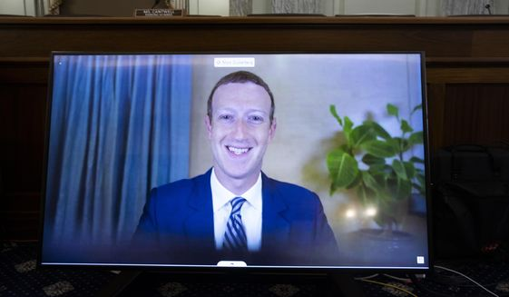 In this Oct. 28. 2020 file photo, Facebook CEO of Mark Zuckerberg appears on a screen as he speaks remotely during a hearing before the Senate Commerce Committee on Capitol Hill in Washington.  (Michael Reynolds/Pool via AP)  **FILE**