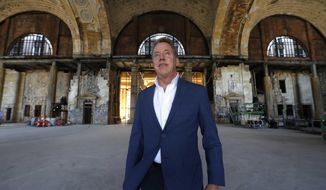 FILE - In this June 14, 2018, file photo, Bill Ford Jr., Ford Motor Company Executive Chairman and Chairman of the Board, poses in the Michigan Central Station in Detroit. Ford Motor Co. is expanding its footprint in Detroit's Corktown neighborhood by adding onto plans that began with its purchase and renovation of the massive and once-derelict station. The Dearborn, Michigan-based automaker also plans to turn a vacant book warehouse into the industrial center for its 30-acre Michigan Central mobility innovation district. Details were released Tuesday, Nov. 17, 2020, and are part of Ford's $740 million project to create an innovation hub to help shape the way people and goods will move around in the future. (AP Photo/Paul Sancya File)