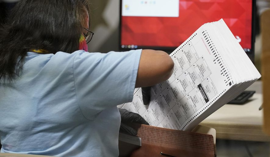 In this Nov. 5, 2020, file photo a county election worker scans mail-in ballots at a tabulating area at the Clark County Election Department, Thursday, Nov. 5, 2020, in Las Vegas. Election-related lawsuits flew Tuesday, Nov. 17, 2020, in Nevada, where a voting watchdog group organized by a conservative Nevada activist is asking a judge to nullify the Nov. 3 statewide election. (AP Photo/John Locher, File)